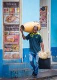 Το άτομο περπατά κάτω από την οδό που φέρνει το τύμπανό του στον ώμο και το καπέλο του Στοκ εικόνες με δικαίωμα ελεύθερης χρήσης