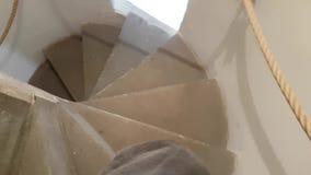 Το άτομο περπατά κάτω από τη στενή σπειροειδή σκάλα απόθεμα βίντεο
