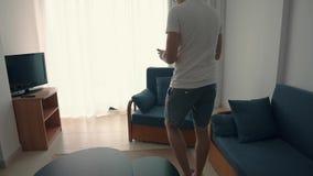 Το άτομο περπατά πέρα από το δωμάτιο, παίρνει το smartphone και κάθεται στην καρέκλα απόθεμα βίντεο