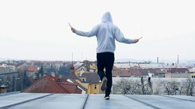Το άτομο πηδά το σχοινί στη στέγη του σπιτιού απόθεμα βίντεο