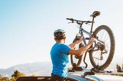 Το άτομο ποδηλατών βουνών παίρνει του ποδηλάτου του από τη στέγη αυτοκινήτων στοκ εικόνα με δικαίωμα ελεύθερης χρήσης