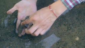Το άτομο που βρίσκεται χρυσό Ο σύγχρονος τυχερός το μεταλλοδίφης βρήκε το μέρος του χρυσού στον κολπίσκο κατά φιλτράρισμα της άμμ φιλμ μικρού μήκους
