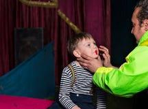 Το άτομο που εφαρμόζει το πρόσωπο κλόουν αποτελεί στο αγόρι Στοκ φωτογραφία με δικαίωμα ελεύθερης χρήσης