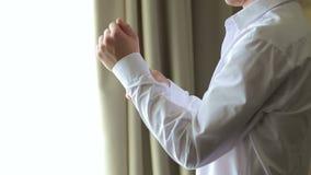 Το άτομο που κουμπώνει τα κουμπιά στα μανίκια του πουκάμισού του που στέκεται κοντά στο παράθυρο απόθεμα βίντεο