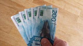 Το άτομο που κρατά τη νέα έκδοση του 2017 των νορβηγικών 200 στέφει το νόμισμα χρημάτων εγγράφου στοκ φωτογραφία με δικαίωμα ελεύθερης χρήσης