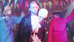 Το άτομο που μεταμφιέζεται ως βαμπίρ χορεύει με ένα κρανίο στο χέρι του απόθεμα βίντεο