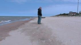 Το άτομο που μιλά στο τηλέφωνο και πηγαίνει στη βάρκα στην παραλία απόθεμα βίντεο