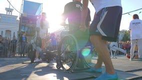 Το άτομο που παρεμποδίζεται στην καρέκλα ροδών συμμετέχει στις συσκευές κατάρτισης στον αθλητικό ανταγωνισμό στο φωτεινό φυσικό φ απόθεμα βίντεο