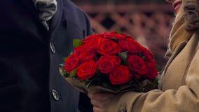 Το άτομο που παρουσιάζει στη φίλη με τη δέσμη των λουλουδιών, εξευγενίζει τα αγκαλιάσματα του ζεύγους ερωτευμένα απόθεμα βίντεο