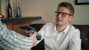 Το άτομο που πληρώνει για τον καφέ με κινητό τηλέφωνο και που χρησιμοποιεί τον αναγνώστη από το σερβιτόρο στον καφέ nfc ανέπαφο απόθεμα βίντεο