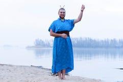 Το άτομο που στέκεται με το χέρι, χαμογελώντας και εξετάζοντας τη κάμερα στην αμμώδη όχθη ποταμού στοκ εικόνες με δικαίωμα ελεύθερης χρήσης