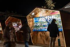 Το άτομο που στέκεται μπροστά από έναν θάλαμο αγοράς Χριστουγέννων κατά τη διάρκεια της νύχτας με μια σακούλα σε δικοί του παραδί στοκ φωτογραφίες
