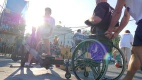 Το άτομο που τίθεται εκτός λειτουργίας στην αναπηρική καρέκλα τραβά το καλώδιο στις συσκευές κατάρτισης στα αθλητικά θεάματα στην φιλμ μικρού μήκους