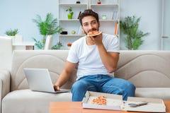 Το άτομο που τρώει την πίτσα που έχει μια take-$l*away στο σπίτι χαλαρώνοντας στήριξη στοκ φωτογραφία
