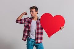 Το άτομο που λυγίζει το μυ του και κρατά μια μεγάλη κόκκινη καρδιά Στοκ Εικόνες