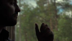 Το άτομο που φαίνεται έξω παράθυρο με το πηγούνι παραδίδει επάνω ένα τραίνο, σοβαρή έκφραση απόθεμα βίντεο