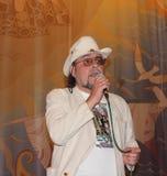 Το άτομο που φορά τα γυαλιά, σε ένα καπέλο, σε ένα άσπρο κοστούμι τραγουδά το τραγούδι σε ένα μικρόφωνο Στοκ Εικόνες