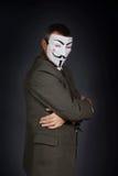 Το άτομο που φορά τη μάσκα του τύπου Fawkes με τα διασχισμένα χέρια στέκεται στο σκοτεινό κλίμα Στοκ εικόνες με δικαίωμα ελεύθερης χρήσης