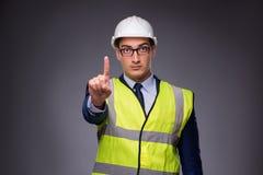 Το άτομο που φορούν το σκληρό καπέλο και η κατασκευή περιβάλλουν Στοκ φωτογραφίες με δικαίωμα ελεύθερης χρήσης