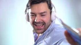 Το άτομο που χορεύει με τα ακουστικά επάνω, αποκόπτει το ευτυχές και εύθυμο, κινούμενο περιστασιακό και βέβαιο άκουσμα χαμόγελου  απόθεμα βίντεο