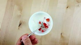 Το άτομο που χρησιμοποιεί ένα κουτάλι για τρώει τις υγιείς φράουλες με το άσπρο γιαούρτι σε σε αργή κίνηση στον ξύλινο πίνακα, έν απόθεμα βίντεο