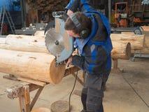 Το άτομο πριονίζει τα ξύλινα κούτσουρα με ένα αλυσιδοπρίονο Στοκ φωτογραφία με δικαίωμα ελεύθερης χρήσης