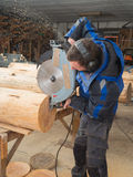 Το άτομο πριονίζει τα ξύλινα κούτσουρα με ένα αλυσιδοπρίονο Στοκ Εικόνες