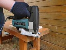 Το άτομο πριονίζει την ξύλινη σανίδα Στοκ Εικόνες