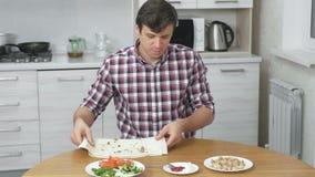 Το άτομο προετοιμάζει τα συστατικά για το shawarma μαγειρέματος στον πίνακα κουζινών στο σπίτι Pita, λαχανικά και πράσινο κρεμμύδ απόθεμα βίντεο