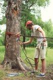 Το άτομο προετοιμάζει τις αποτυπώσεις εξοπλισμού εξασφαλίζει το σχοινί στο δέντρο Στοκ εικόνες με δικαίωμα ελεύθερης χρήσης