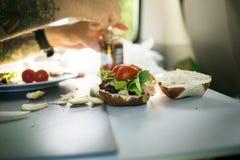 Το άτομο προετοιμάζει burger κατά τη διάρκεια στρατοπεδεύοντας van trip στοκ φωτογραφία