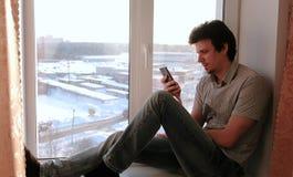 Το άτομο προσέχει κάτι στο διαδίκτυο σε κινητό του καθμένος σε ένα windowsill Στοκ Εικόνες