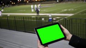 Το άτομο προσέχει την πράσινη ταμπλέτα οθόνης σε μια σύνοδο πρακτικής ομάδας ποδοσφαίρου από τους λευκαντές φιλμ μικρού μήκους