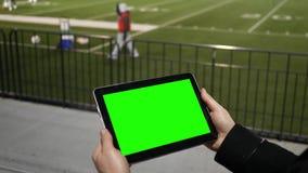 Το άτομο προσέχει την πράσινη ταμπλέτα οθόνης σε μια σύνοδο πρακτικής ομάδας ποδοσφαίρου από τους λευκαντές απόθεμα βίντεο