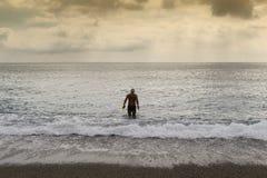 Το άτομο πρόκειται να κολυμπήσει στη θάλασσα στο ηλιοβασίλεμα στοκ εικόνες με δικαίωμα ελεύθερης χρήσης