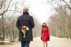 Το άτομο πρόκειται να προσφέρει τα λουλούδια στη φίλη του Στοκ φωτογραφία με δικαίωμα ελεύθερης χρήσης