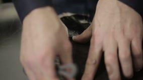 Το άτομο ράβει τα ενδύματα Έκοψε ένα κομμάτι του δέρματος με τη γούνα κλείστε επάνω απόθεμα βίντεο