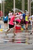 Το άτομο ρίχνει το μπαλόνι νερού στην πάλη ομάδας μετά από 5K τη φυλή Στοκ Εικόνα