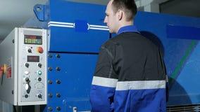 Το άτομο ρυθμίζει τη λειτουργία της μηχανής για το μέταλλο φύλλων σε μια μεγάλη υδραυλική ψαλίδα λαιμητόμων Το σιδέρωμα πιέζει απόθεμα βίντεο