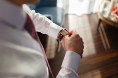 Το άτομο σε ένα άσπρες πουκάμισο και μια φανέλλα εξετάζει τα ακριβά ρολόγια ρολόι σχεδιαστών κινηματογραφήσεων σε πρώτο πλάνο σε  στοκ εικόνα με δικαίωμα ελεύθερης χρήσης