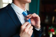 Το άτομο σε ένα κλασικό κοστούμι ισιώνει τον μπλε δεσμό του Όμορφο κομψό νέο άτομο μόδας στο κλασσικά κοστούμι και το τόξο τ κοστ στοκ εικόνες