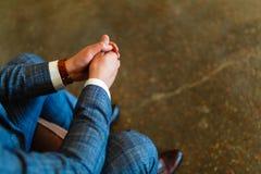 Το άτομο σε ένα κοστούμι κάθεται με τα χέρια του στα γόνατά του Βάζοντας τα χέρια σας από κοινού Βλαστός ενός ατόμου σε μια συνεδ στοκ εικόνα με δικαίωμα ελεύθερης χρήσης