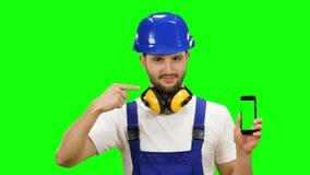 Το άτομο σε ένα κοστούμι οικοδόμων ` s διαφημίζει ένα smartphone πράσινη οθόνη Χλεύη επάνω φιλμ μικρού μήκους