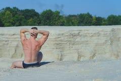 Το άτομο σε ένα κοστούμι λουσίματος κάθεται υψηλό σε έναν λόφο άμμου Στοκ Εικόνες