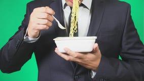 Το άτομο σε ένα κοστούμι τρώει τα κινεζικά νουντλς, κινηματογράφηση σε πρώτο πλάνο, 4k, πράσινο υπόβαθρο, σε αργή κίνηση, διάστημ απόθεμα βίντεο