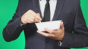 Το άτομο σε ένα κοστούμι τρώει τα κινεζικά νουντλς, κινηματογράφηση σε πρώτο πλάνο, 4k, πράσινο υπόβαθρο, σε αργή κίνηση, διάστημ φιλμ μικρού μήκους