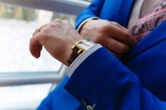 Το άτομο σε ένα μπλε ακριβές κοστούμι και μια φανέλλα εξετάζει τα ακριβά ρολόγια ρολόι σχεδιαστών κινηματογραφήσεων σε πρώτο πλάν στοκ φωτογραφία με δικαίωμα ελεύθερης χρήσης