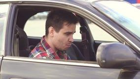 Το άτομο σε ένα πουκάμισο πίνει σε ένα οινόπνευμα αυτοκινήτων φιλμ μικρού μήκους