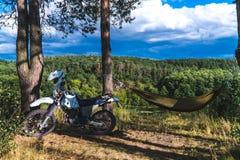 Το άτομο σε μια αιώρα στο δασικό βουνό πεύκων, υπαίθριος ταξιδιώτης χαλαρώνει, enduro από την οδική μοτοσικλέτα στοκ φωτογραφία με δικαίωμα ελεύθερης χρήσης