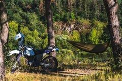 Το άτομο σε μια αιώρα στο δασικό βουνό πεύκων, υπαίθριος ταξιδιώτης χαλαρώνει, enduro από την οδική μοτοσικλέτα στοκ εικόνες